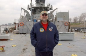 Whicker stands in front of the LST-325, the WWII-era vessel that he saves from Erika Lehmann in his new novel
